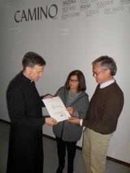 El párroco entrega el certificado donde consta el número y el colaborador